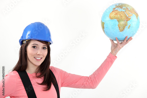 Construction worker holding a globe.