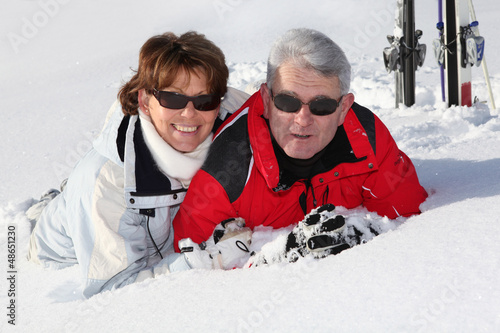 Older couple lying in the snow