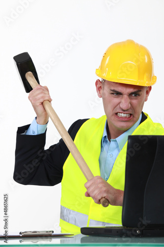 furious businessman smashing his laptop with a hammer