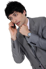 confused businessman talking on his cell