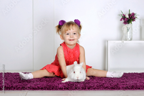 Smiling little girl and white rabbit