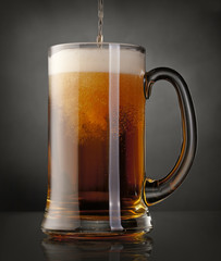 Mug of beer over black background