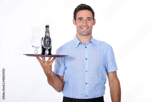 A waiter bringing a bottle of liquor.