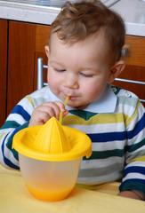 Pequeño niño bebiendo jugo de naranja.