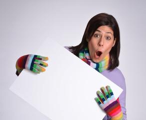 Expresiva mujer en otoño,invierno sujetando un panel blanco.