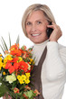 mature florist holding bouquet