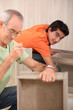 Grandfather with grandson assembling furniture