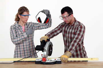 Woman making sure man uses hearing protection