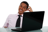 Happy young businessman scratching head