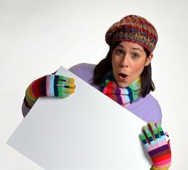 Joven mujer en otoño,invierno sujetando un panel blanco