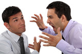 Man yelling at his apathetic colleague