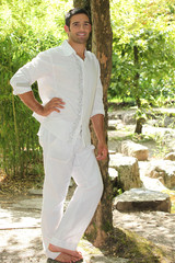 Man dressed in white stood in forrest