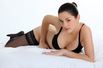 Woman lying on a bed in her underwear
