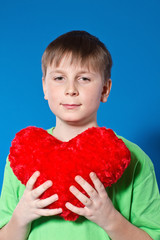 boy holding a heart on a blue background