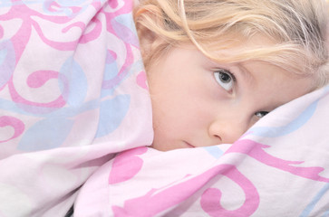 Child lying in bed with a pink quilt.