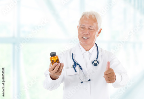 Thumb up Asian doctor holding bottle pills