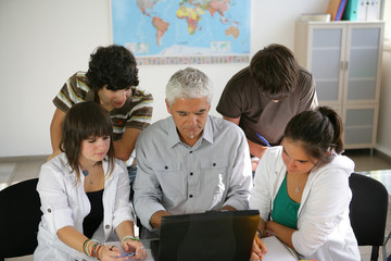 Teacher and a group of pupils sitting round a laptop