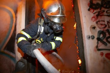 Fireman extinguishing fire inside an old house