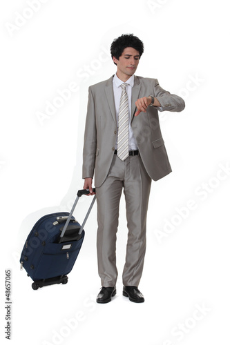 Businessman with a suitcase looking at his watch
