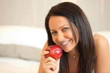 Portrait of smiling woman holding apple