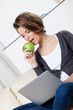 Sitting on the sofa beautiful woman eats a green apple
