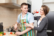 Man in apron cooks dinner for his girlfriend in the kitchen