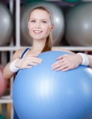 Athletic woman with blue gym ball in fitness gym