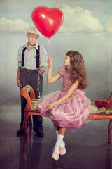 The boy gives a balloon to the girl