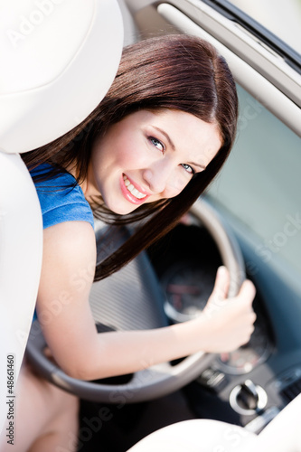 Portrait of young female driver turning back