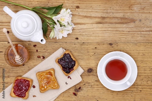 breakfast table with tea, teapot, cup of tea, jam, bread and hon