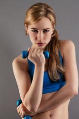 junge ernste sportlerin mit fitness hanteln