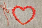Heart in shape of red buttons and darning needle