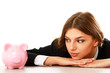 Young beautiful woman sitting with piggy bank
