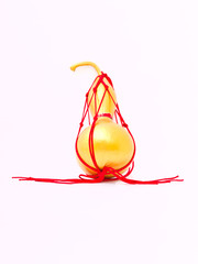 A golden dried calabash wraped by red thread isolated on white