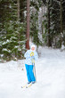 Happy young skier with ski poles in hands up in winter forest