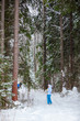 Happy young woman standing on ski in deep winter forest
