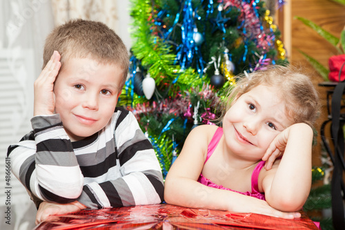 Brother and sister with presents sitting near Christmas tree