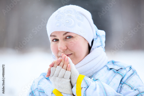 Young woman warming fingers with ski poles in hands