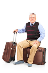 A mature man resting seated on a travel bag