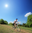 Male bicyclist riding a mountain bike down hill on a sunny day