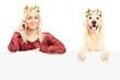 Royal female and dog wearing crowns and posing behind panel
