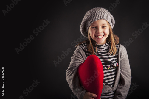 Lovely young girl with red heart on black background.