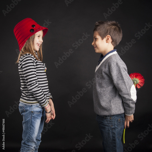 Lovely couple of kids. Boy offering flower on black background.
