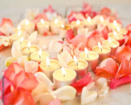 Herz aus Kerzen und Rosenblütenblättern