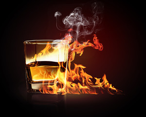 Glass of burning yellow absinthe
