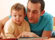 Padre e hijo compartiendo y leyendo un cuento.