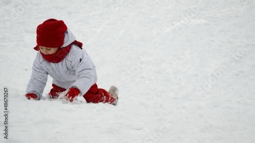 little girl climbing up a snowy hill