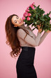 Happy vivacious woman with pink roses