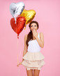 Cute woman with heart shaped party balloons