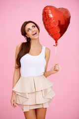 Vivacious brunette with a red heart balloon